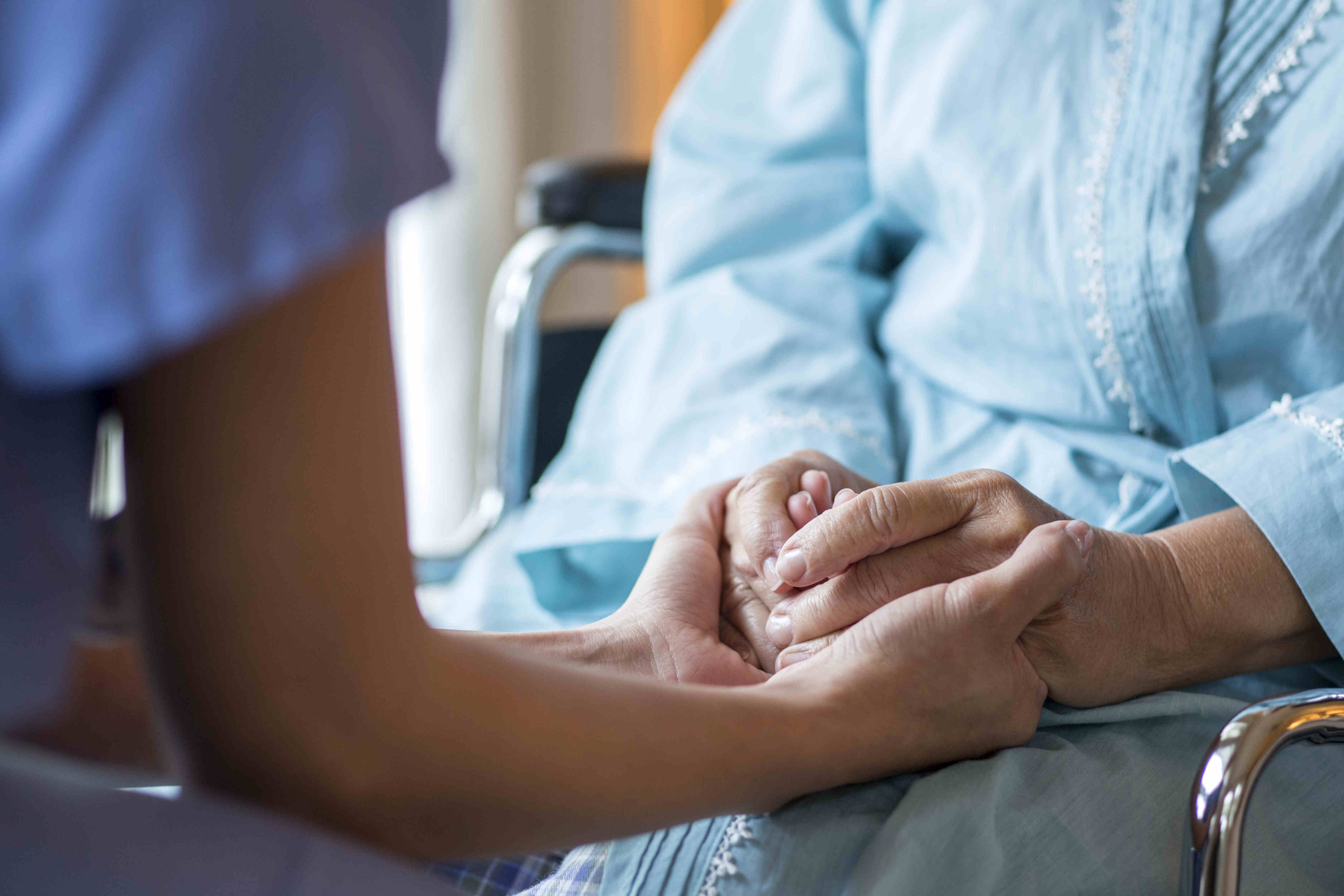 stock-photo-close-up-of-nurse-comforting-older-patient-in-wheelchair-113858147_副本
